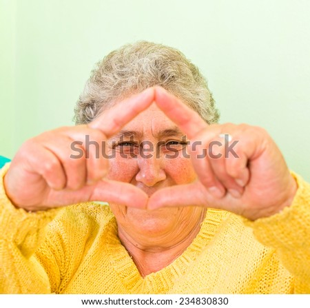 Happy elderly woman showing frame with her fingers - stock photo