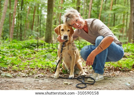 Happy elderly woman sitting with labrador retriever in a forest - stock photo