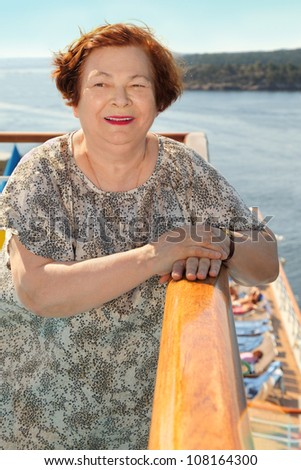Happy elderly woman stands at board of ship and looks into distance - stock photo