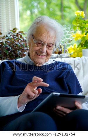 Happy Elderly woman using a tablet and laughing - stock photo