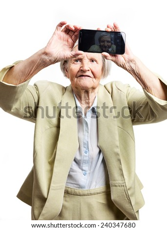 Happy elderly woman using touch screen mobile for taking selfie - stock photo