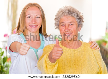Happy elderly woman with her carer showing thumbs up