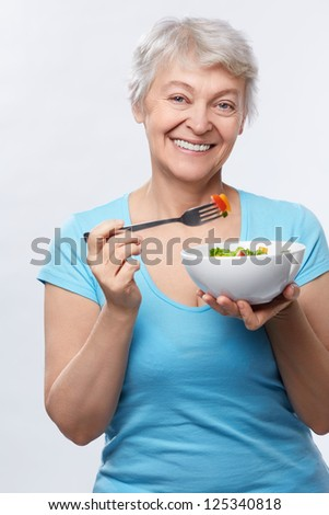 Happy elderly woman with salad on white background - stock photo