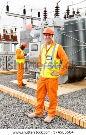 happy electrical engineer in substation with colleague on background - stock photo