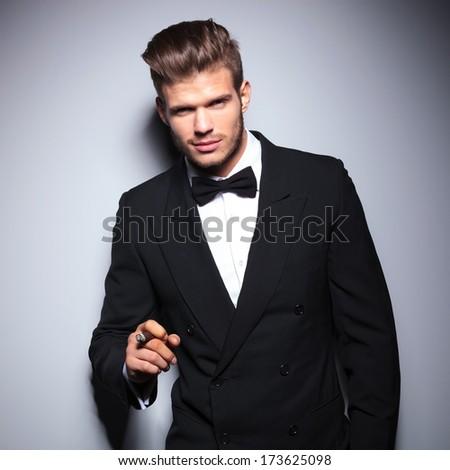 happy elegant fashion man in tuxedo smiling while smoking a cigar - stock photo