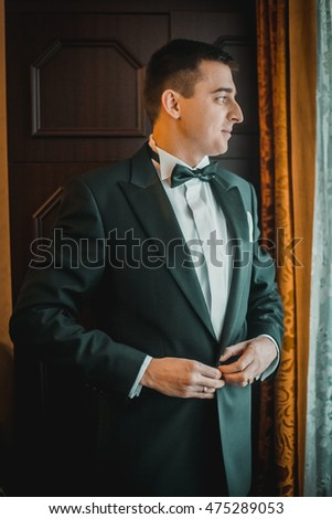 happy elegant groom getting ready in the morning at window light in rich room