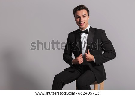 happy elegant man in tuxedo and bowtie holding collar while sitting on chair on grey background