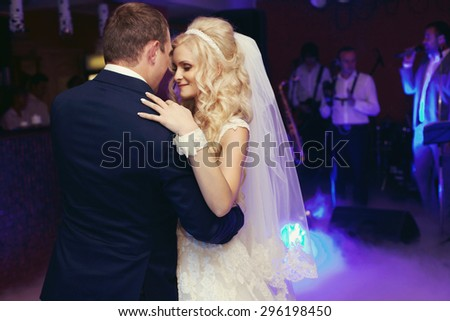 happy elegant married couple dancing and kissing in a restaurant, celebrating wedding - stock photo