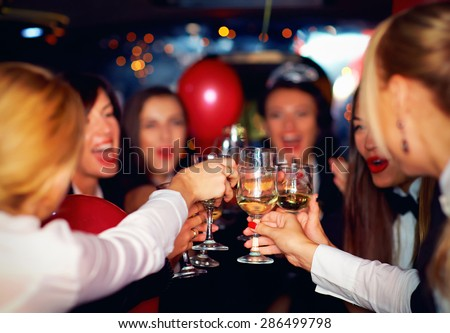 happy elegant women clinking glasses in limousine, focus on glasses