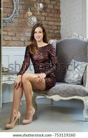 Happy elegant young white woman sitting in armchair, smiling.