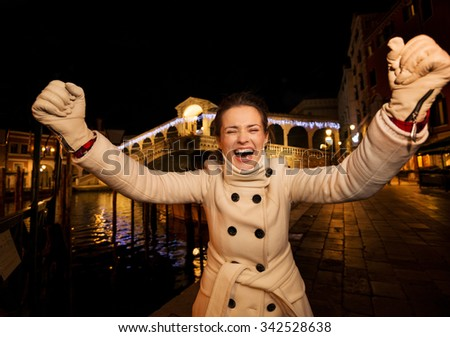 Happy elegant young woman in white coat rejoicing while standing in front of Rialto Bridge in the evening. She having Christmas time trip and enjoying stunning views of Venice, Italy