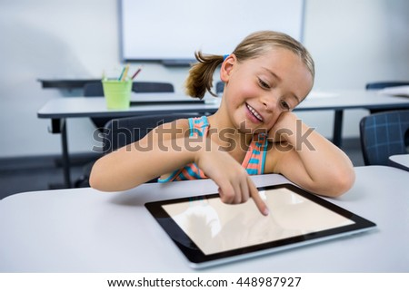 Happy elementary girl using digital tablet in classroom