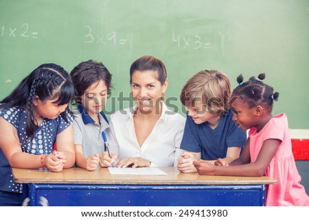 Happy elementary multi ethnic students with their female teacher at classroom desk. - stock photo
