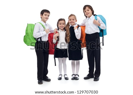 Happy elementary school kids with colorful back packs - isolated - stock photo