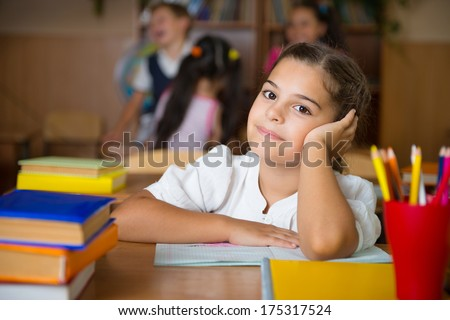 Happy elementary students at school after classes. Background is dark. - stock photo