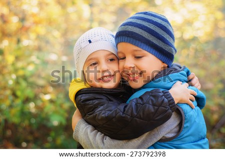 Happy embracing children, walking in the autumn park