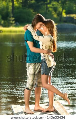 Happy embracing teens standing barefoot  on pier - stock photo