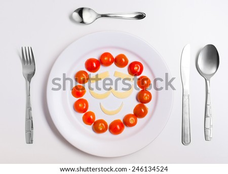 happy emoticon food, made from cheese and tomatoes, on a plate with cutlery, isolated