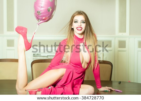 Happy emotional glamour smiling young woman with long hair straight body and slim legs in red dress and shoes with birthday holiday ballon on heel sitting on table indoor, horizontal picture