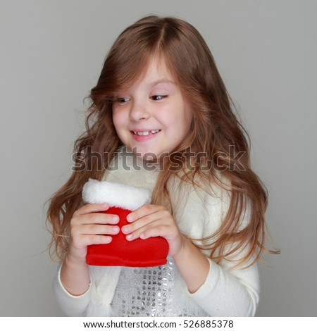 Happy emotional little girl holding christmas red boot and looks for a gift on a gray background oh Holiday