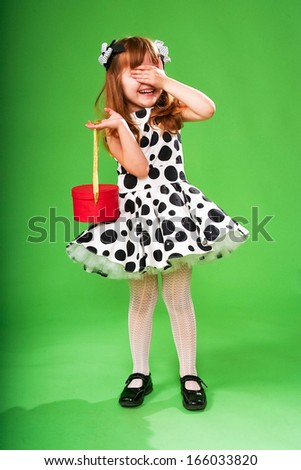Happy emotional little girl holding christmas red box on a green background. Model in vintage black and white dress with peas print.  - stock photo