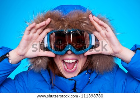 happy emotional woman in ski glasses and winter coat over blue background - stock photo