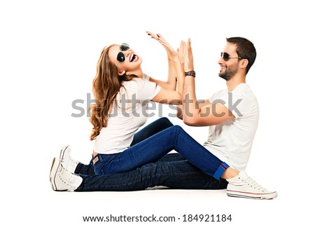 Happy emotional young couple in love posing at studio. Isolated over white.