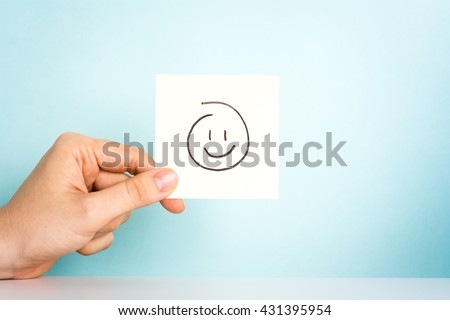 Happy employee. Hand holding a illustration of a happy emoticon or icon on blue background. - stock photo