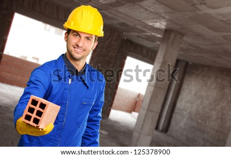 Happy Engineer Holding Brick, Indoors