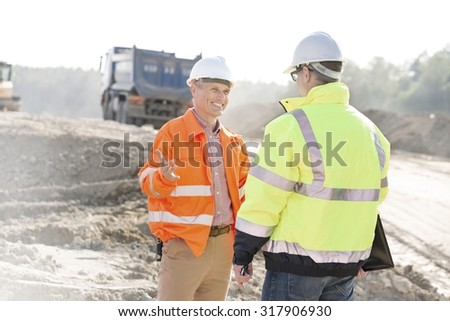 Happy engineer talking to colleague at construction site on sunny day