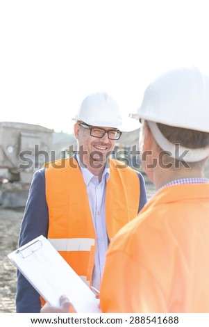 Happy engineers discussing at construction site against clear sky - stock photo