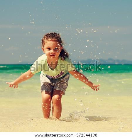 Happy enjoying kid girl playing and splashing with water on blue sea background - stock photo