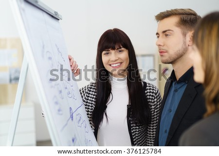 Happy enthusiastic young businesswoman having a meeting with two colleagues in front of a flip chart as they discuss their strategy - stock photo