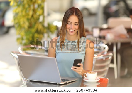 Happy entrepreneur working with a phone and laptop in a coffee shop in the street - stock photo