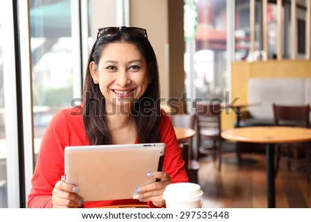 Happy entrepreneur working with a phone and tablet in a coffee shop in the street
