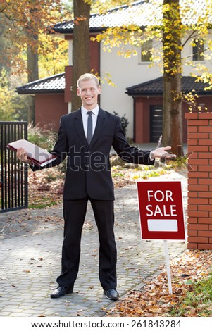 Happy estate agent during his work outside the house