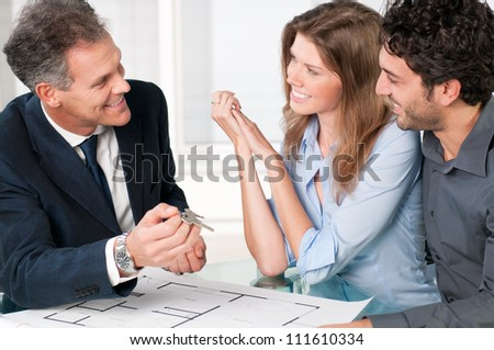 Happy estate agent showing new home keys to a young couple