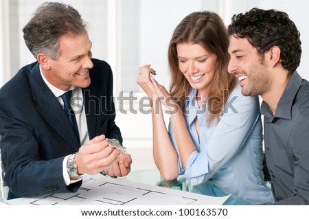 Happy estate agent showing new home keys to a young couple after a discussion on house plans. - stock photo