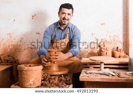 happy european artisan man creating ceramic piece on spinning pottery wheel in workshop