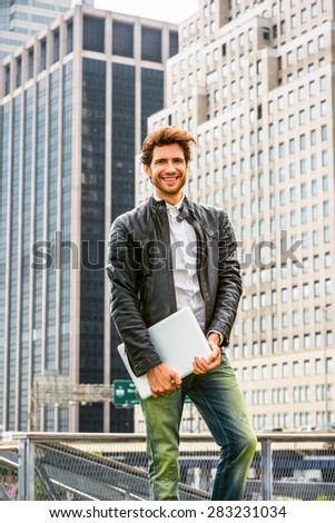 Happy European businessman in New York. Wearing black leather jacket, blue jeans, hands carrying laptop computer, a young guy with beard, standing in business district, confidently looking forward. - stock photo