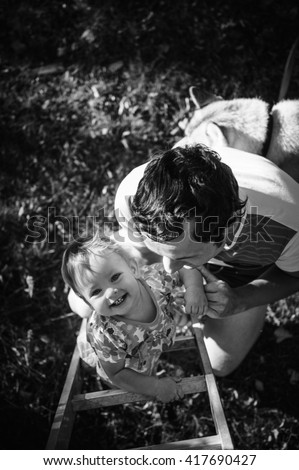 Happy european child climbing the vertical ladder. Father helps and protects his adorable little kid. Playground outdoors. Walk in the fresh air. Daughter, baby, girl. Photo in black and white