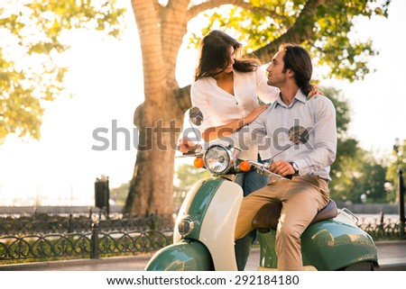 Happy european couple flirting on scooter in the town - stock photo