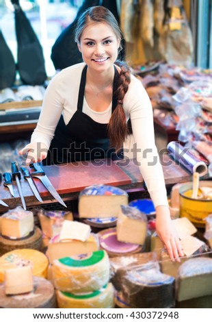 happy european female brunette with different types of cheese in gastronomy