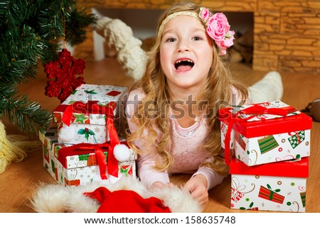 Happy european girl with long blond curly hair and flower on it lies under Christmas tree with her presents and screams gaily - stock photo
