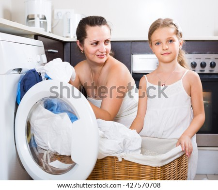 Happy european  housewife and her daughter with linen near washing machine  - stock photo