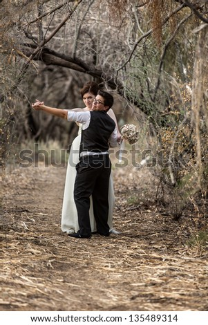 Happy European Lesbian couple dancing in forest - stock photo
