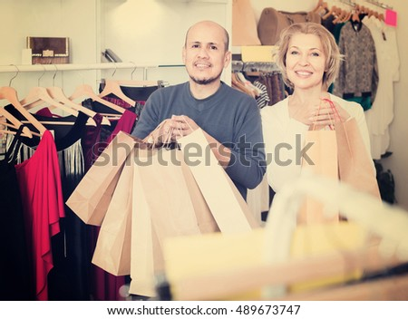 Happy european senior couple with purchases in bags at apparel store