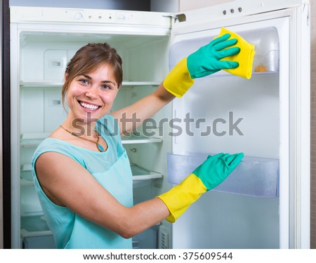 Happy european woman cleaning empty refrigerator indoors