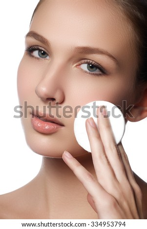 Happy european woman with cotton pad, isolated on white background. Beauty fresh girl cleaning face with cotton swab. Beautiful young woman cleaning her face with cotton