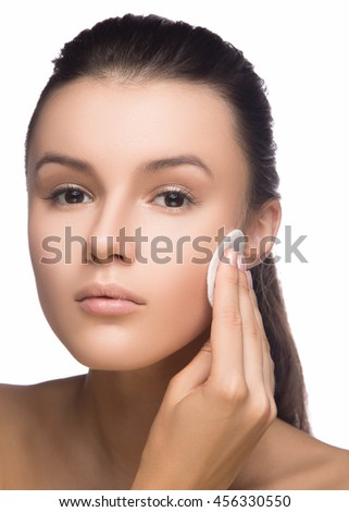Happy european woman with cotton pad, isolated on white background. Beauty fresh girl cleaning face with cotton swab. Beautiful young woman cleaning her face - stock photo